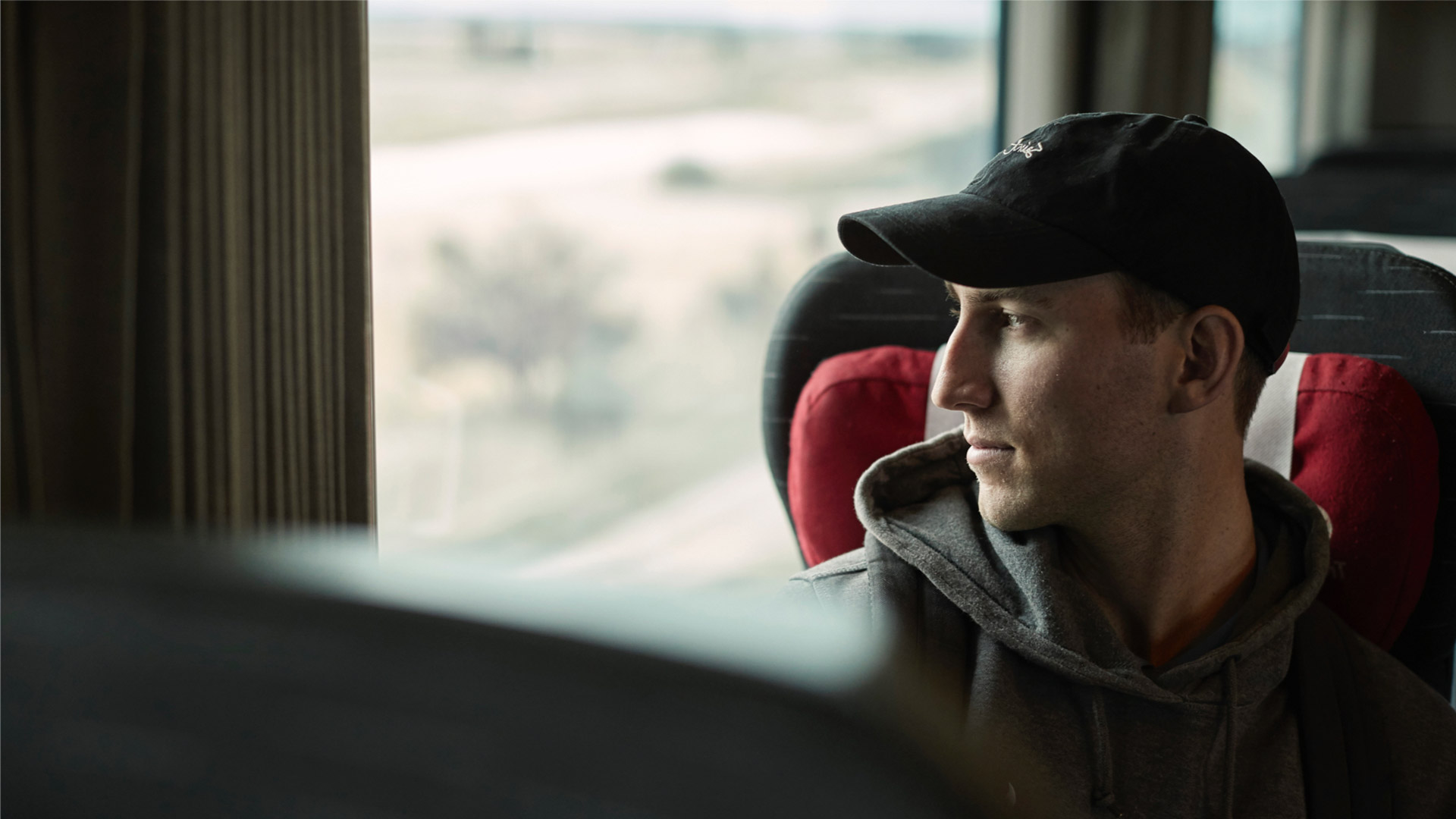 Man wearing baseball cap looking out train window